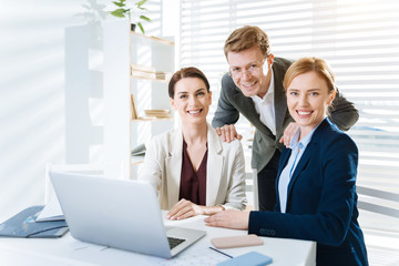 Working in team. Satisfied merry three colleagues smiling while gazing at the camera and man placing hands on women shoulders