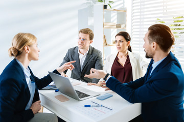 New business style.  Surprised young female colleague telling news while her colleagues sitting at the table and listening