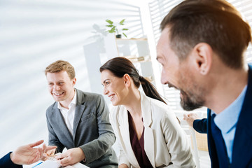 Job interview. Happy cheerful three colleague listening to candidate while sitting and smiling