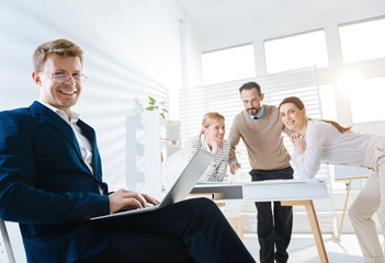 Work online.Confident cheerful male colleague typing while smiling and staring at the camera