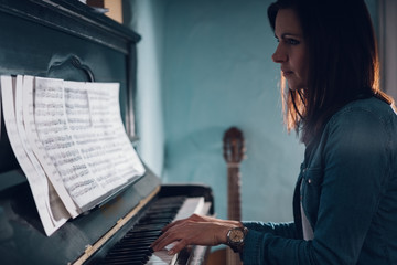 Side view of a beautiful woman playing piano