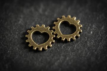 Zahnräder mit Herzchen als Symbol für Partnerschaft und Liebe