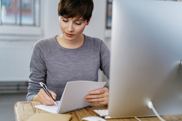 Busy young woman writing at office desk