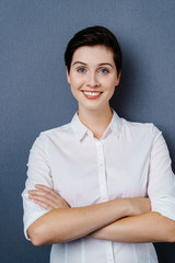 Smiling woman in white shirt with arms folded