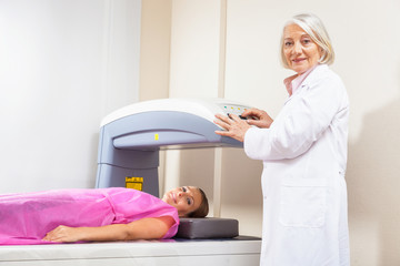 Woman in 40s undergoing medical x-ray with elderly doctor