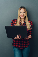 Portrait of a cheerful woman holding a laptop