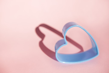 Blue heart with shadow on pink background, symbol of love