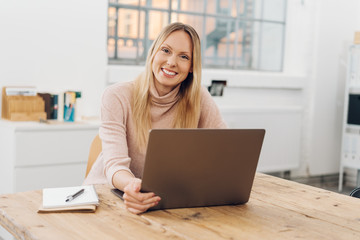 Smiling happy woman in a large airy modern office