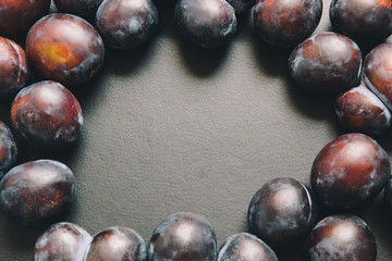 Black textured background with plums around