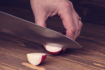 woman's hand cut radishes on a wooden board