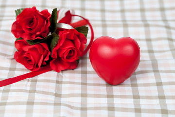 Red rose flower and red heart sign on table cloth