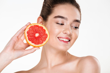 Beauty portrait of pretty smiling woman with soft skin holding juicy grapefruit near her face and looking down isolated over white background