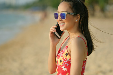 girl happy talk mobile phone on the beach with evening time by wear sunglasses