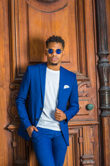 African American Businessman with little goatee working in New York, wearing blue suit, unbuttoned, white collarless shirt, blue sunglasses, standing against vintage office door, thinking. .