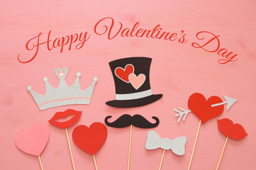Top view Valentine's day background with funny photo booths props: gentleman hat, mustache, heart with arrow and crown.