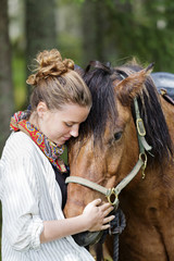 Young blonde woman embracing chestnut horse in forest