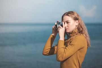 beautiful blonde girl on a sea beach with a old camera in hand