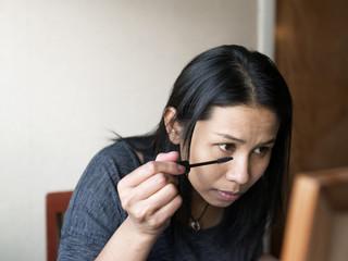 Woman painting eyelashes with mascara