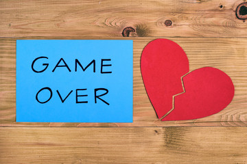 Broken heart and blue paper with text game over on wooden table,relationship breakup concept.