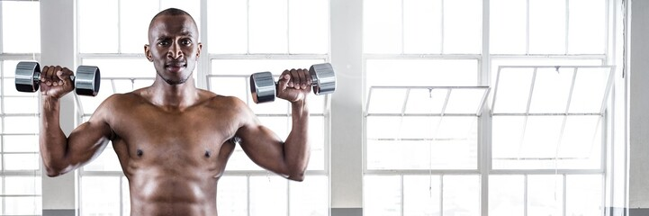 Fit strong Man in gym lifting weights