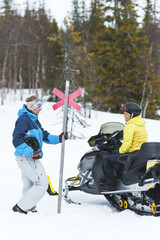 Woman sitting on snowmobile talking with woman holding ski trail pole marker