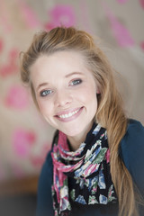 Portrait of young blonde woman with floral scarf smiling