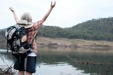 traveler hiker man with backpack raise hands near lake. tourist backpacker relaxing in forest. travel lifestyle, summer vacation concept