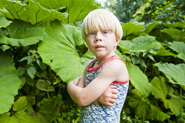 Blonde boy standing by green leaves
