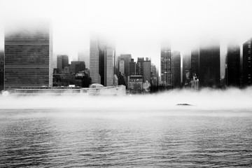 Aluminium Prints New York A dense fog covered New York City during the winter's day on January of 2018. View of Manhattan and United Nations building.