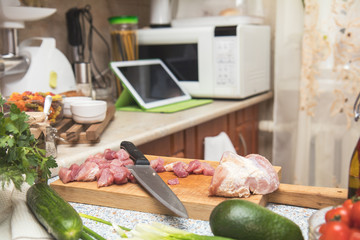 Fresh meat and knife on cutting board in the kitchen table.Small cozy kitchen with household appliances. Cozy home concept
