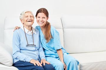 Pflegehilfe und lachende  glückliche Seniorin