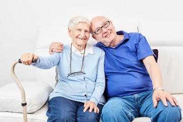 Alter Mann und alte Frau kuscheln liebevoll