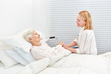 Frau macht Krankenbesuch bei bettlägeriger Seniorin