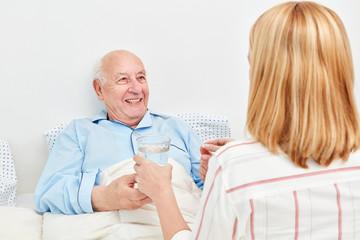 Kranker Senior im Bett nimmt ein Medikament ein