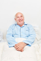 Alter Mann liegt krank im Bett im Seniorenheim