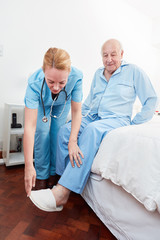 Altenpfleger im Seniorenheim hilft einem Senior