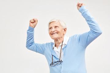 Seniorin jubelt mit geballten Fäusten