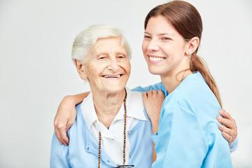 Pflegehilfe und glückliche Seniorin umarmen sich