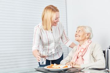 Junge Frau serviert Seniorin ein Mittagessen