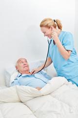 Krankenschwester untersucht kranken Senior
