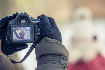 hands in mittens holding a professional camera, the screen image of posing models, winter day