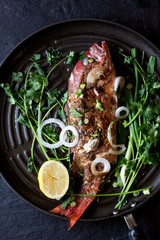 Grilled Whole Red Snapper with Ginger Soy Sauce and Garnish. Served hot in the Frying Pan.