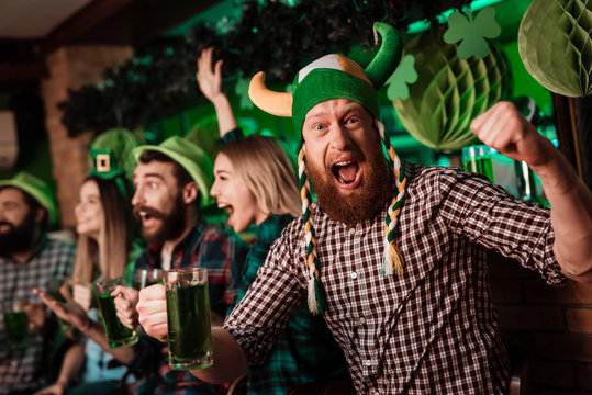 A man in a funny hat celebrates St. Patrick's Day with friends.