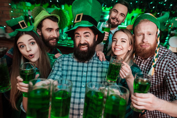 A company of young people posing on the camera with glasses of beer in their hands. Wall mural