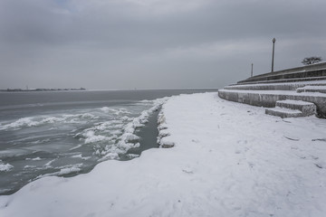 Snow covered walkway next to lake with ice sheets