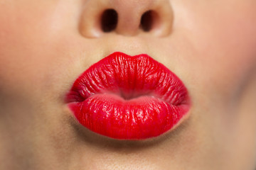 woman lips with red lipstick making kiss