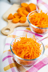 Grate  carrots in a bowl