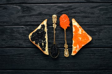 Sandwich with caviar. Caviar on a spoon. On a wooden background. Top view. Free space for text.