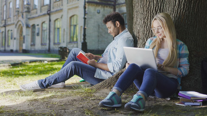 Young male sitting under tree with book near female with laptop, student life