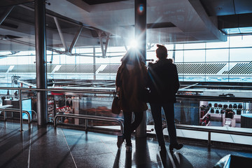 Rear view of silhouettes of two girls in warm clothes standing in airport terminal near glass over duty-free zone and looking at parked airplanes and runway behind windows in defocused background